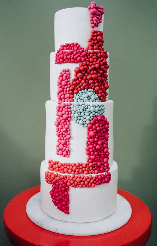 The wedding cake was a large one decorated with red, pink and blue edible beads with a color block effect