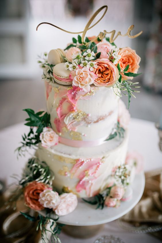 a beautiful spring or summer two-tier wedding cake with bright watercolors, gold, pearls, fresh blooms and greenery and a calligraphy topper