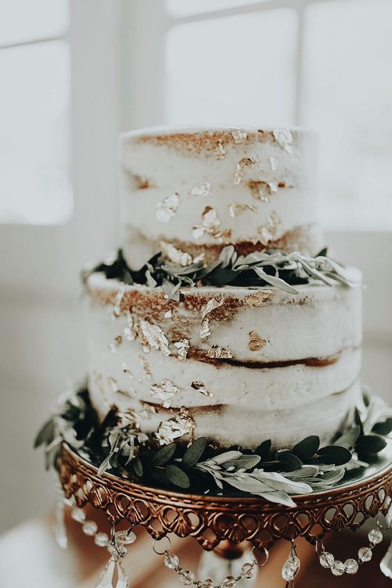 a beautiful two-tier naked wedding cake with edble gold and greenery is a lovely idea for many weddings