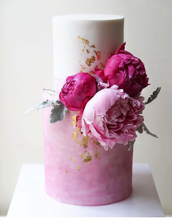 a beautiful white and watercolor pink wedding cake with gold leaf and bold pink and light pink peonies is a gorgeous idea for summer