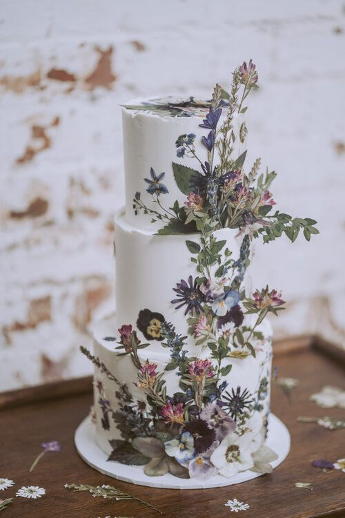 a boho summer three-tier wedding cake with dried blooms and leaves, pressed and dimensional, looks beautiful