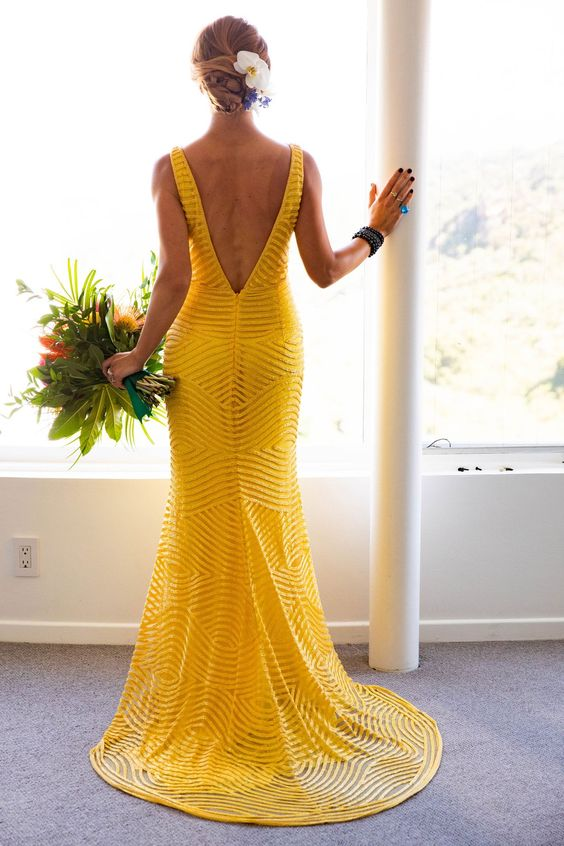 a bold yellow mermaid wedding dress with a pattern, a cutout back, no sleeves is a bold idea for a tropical bride