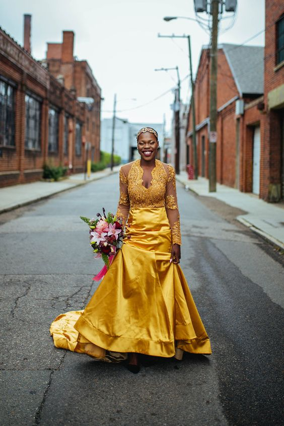 a bold yellow mermaid wedding gown with a fully embellished lace bodice with long sleeves and a plain skirt with a train