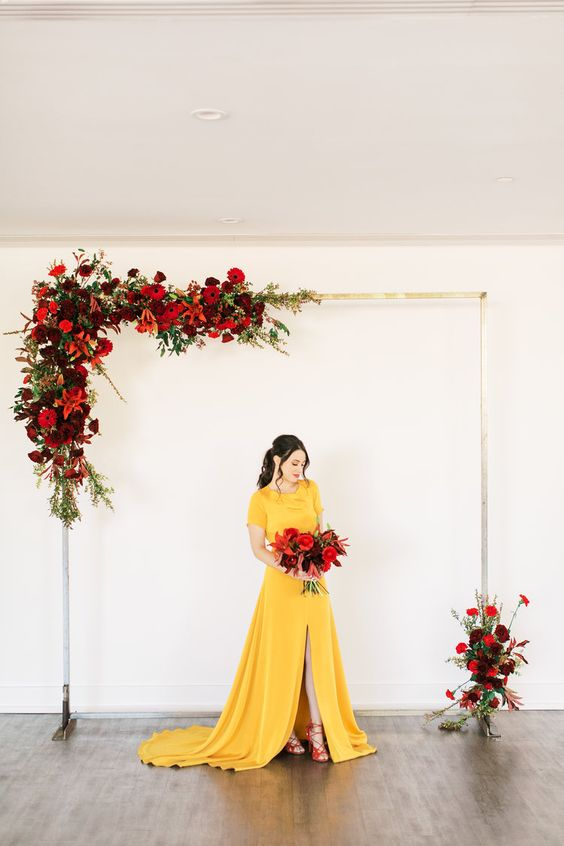 a bold yellow plain A line wedding dress with a high neckline, short sleeves, a front slit and a train plus red lace up shoes