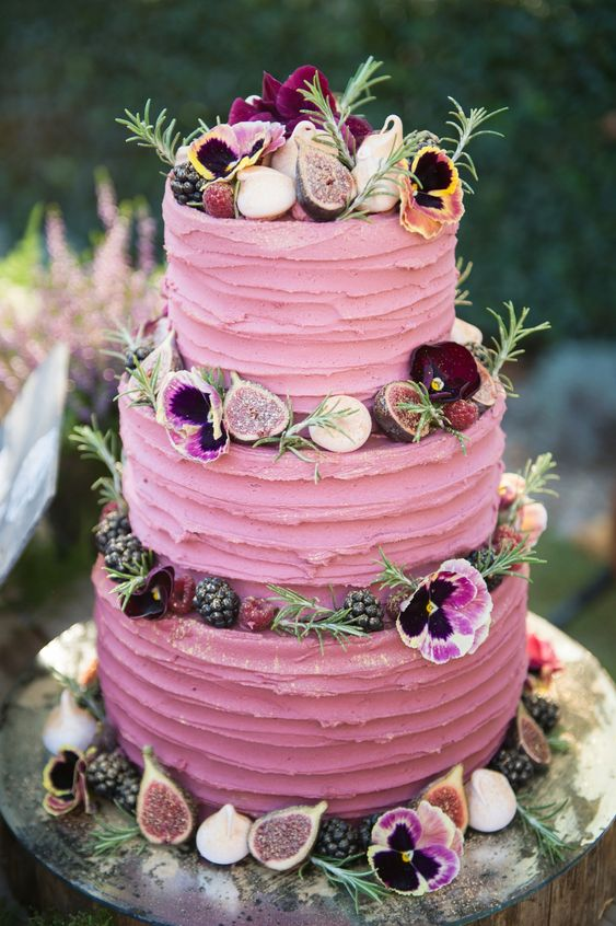 a bright pink textural wedding cake with greenery, blooms, fresh berries and mini meringues is a fantastic and chic idea