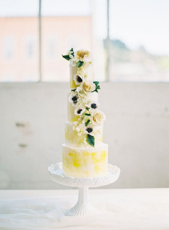 a bright spring five tier wedding cake with bold yellow touches, neutral blooms and leaves is a real masterpiece