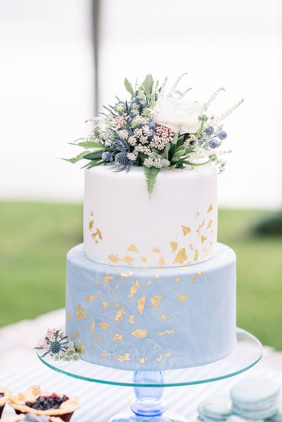 a catchy spring or summer two-tier wedding cake with a white and watercolor blue tier, some greenery, thistles, berries and a bloom on top