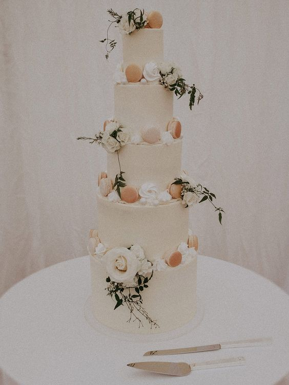 a chic and delicate five tier wedding cake decorated with neutral blooms, with creamy and peachy macarons and greenery is wow