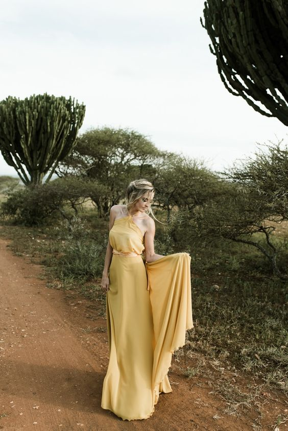 a chic pale yellow A-line wedding dress with a halter neckline and a train for a boho or desert wedding