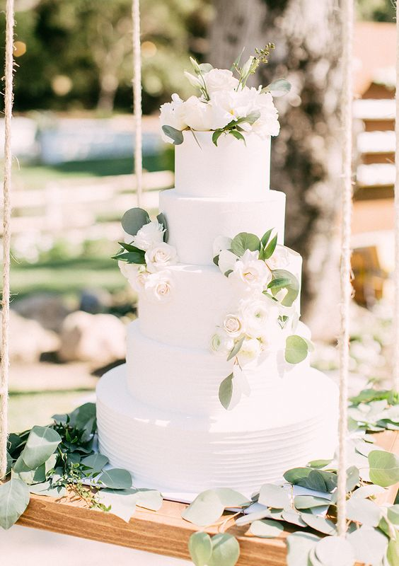 a classic five tier wedding cake, a white textural buttercream one, with fresh neutral blooms and greenery