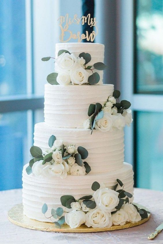 a classic four tier white textural wedding cake with white blooms and foliage plus a calligraphy topper is a beautiful idea