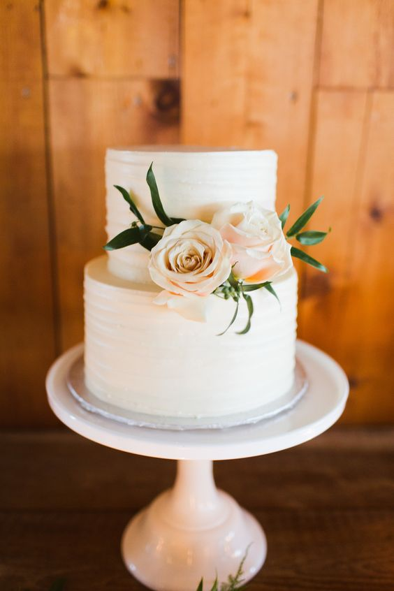 a classic white two-tier wedding cake with a texture and some pastel blooms is a beautiful idea for many wedding styles