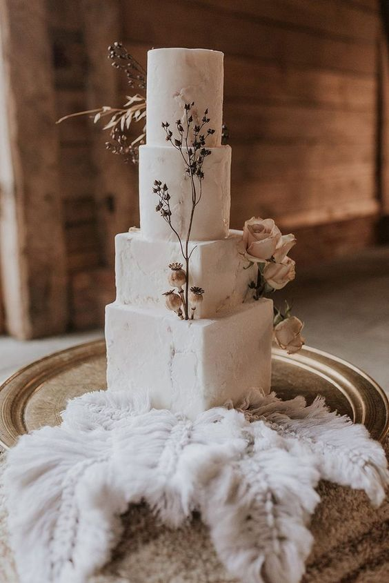 a delicate four tier wedding cake with square and round tiers, sugar patterns, dried blooms and herbs is a stunning idea