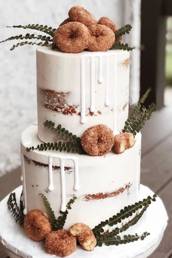 a delicious-looking naked two-tier wedding cake with creamy drip, crusty donuts and greenery is a very chic and lovely idea