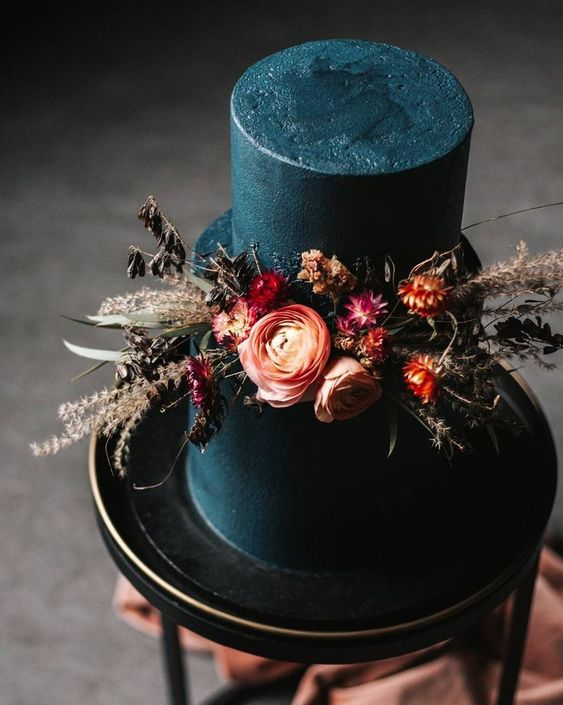 a dramatic matte black wedding cake with bold fresh and dried blooms and foliage is a very chic and stylish idea