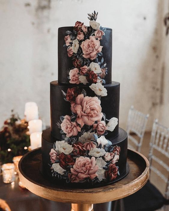 a dramatic three-tier wedding cake in black, with painted and sugar blooms covering it is a very statement-like dessert