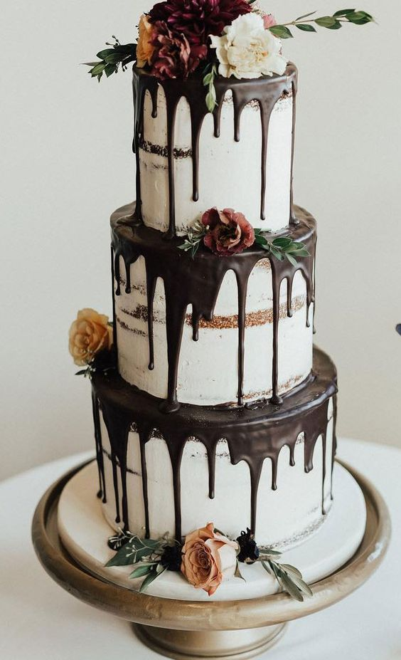 a fantastic three-tier naked wedding cake with chocolate drip, blooms, greenery is a gorgeous idea for many weddings