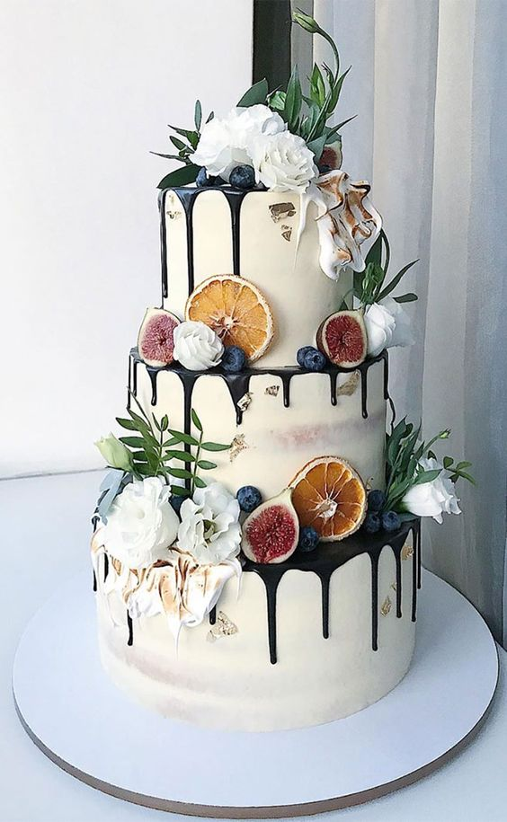 a fantastic three-tier wedding cake with chocolate drip, berries, citrus slices, figs, white blooms and greenery