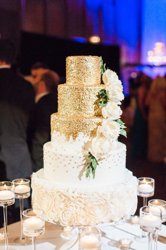 a glam five tier wedding cake with polka dot, ruffle flower and fulyl gold tiers plus sugar blooms is very beautiful