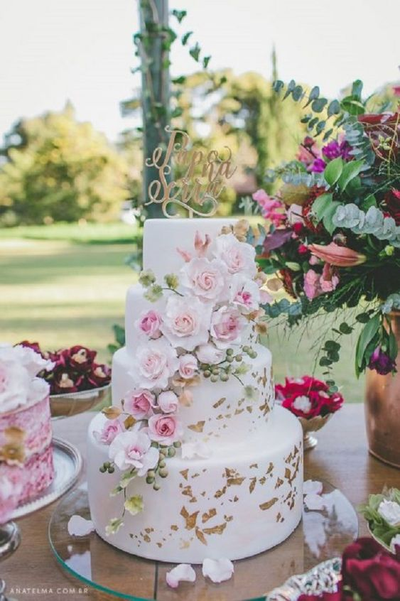 a glam four tier wedding cake with light pink blooms and berries and gold leaf and a calligraphy topper is a lovely idea