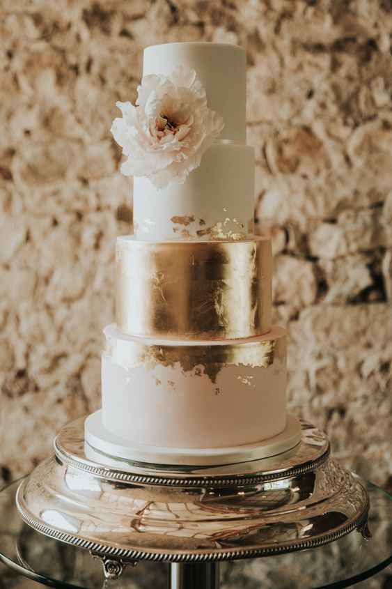 a glam four tier wedding cake with white, blush and gold tiers, gold leaf and a large blush bloom