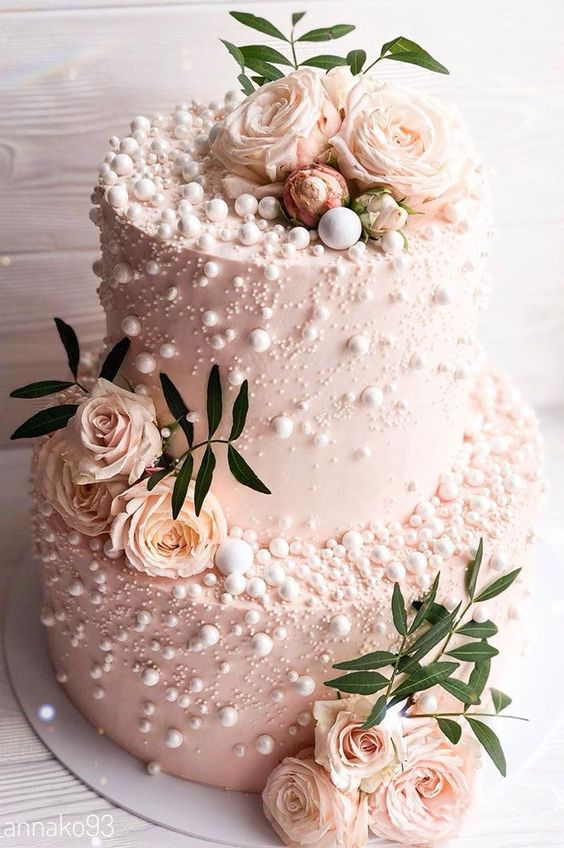 a glam pink two-tier wedding cake covered with beads and pearls, with pastel blooms and greenery is a very beautiful idea