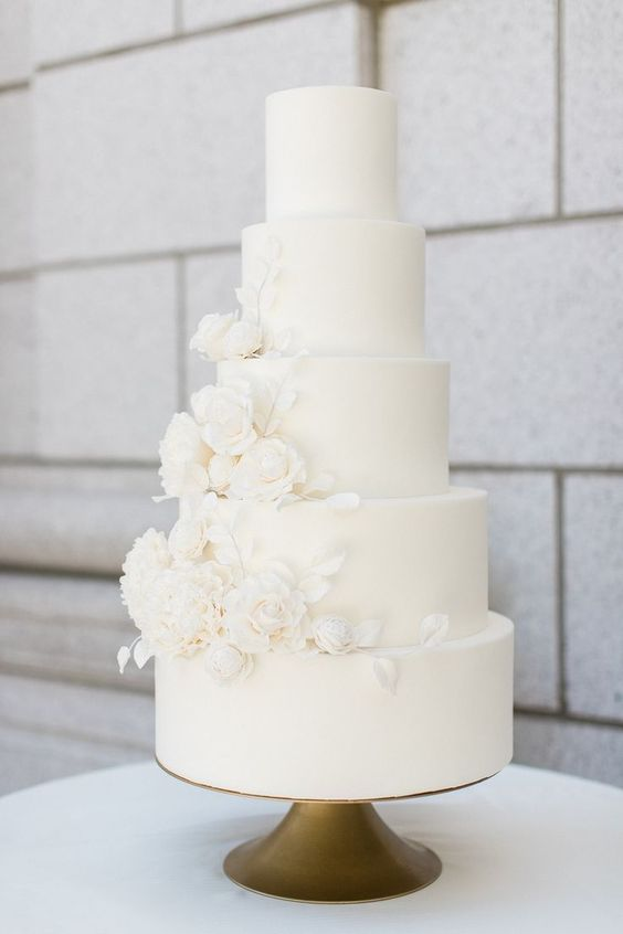 a gorgeous white plain five tier wedding cake decorated with white sugar blooms and leaves is a very chic idea