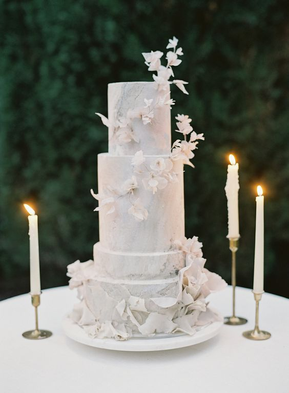 a grey marble four tier wedding cake with dried white blooms and petals is a very refined and chic idea for a modern sophisticated wedding