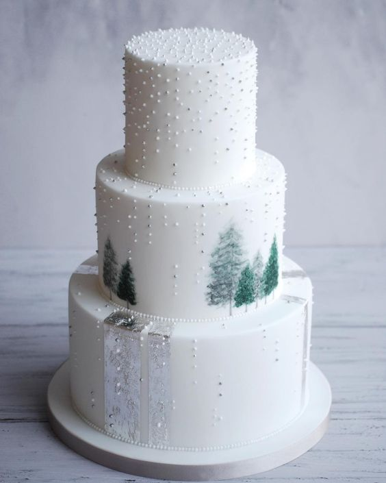 a jaw-dropping three-tier wedding cake with beads, mini trees, silver ribbons is a lovely idea for a chic winter wedding