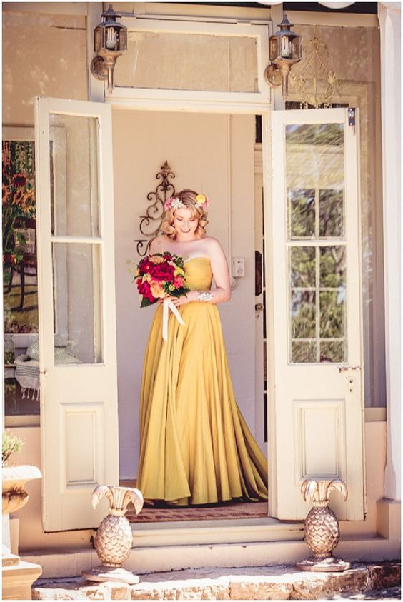 a jaw dropping yellow strapless wedding dress with a draped bodice and a pleated skirt plus a train is wow