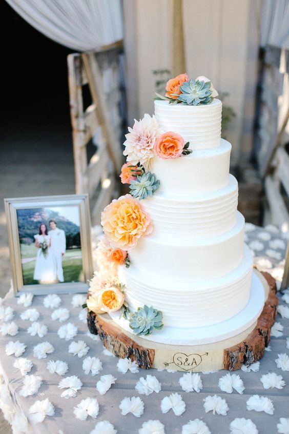 a lovely bold five tier wedding cake with textural tiers, succulents and bold peachy blooms is a chic and bold idea