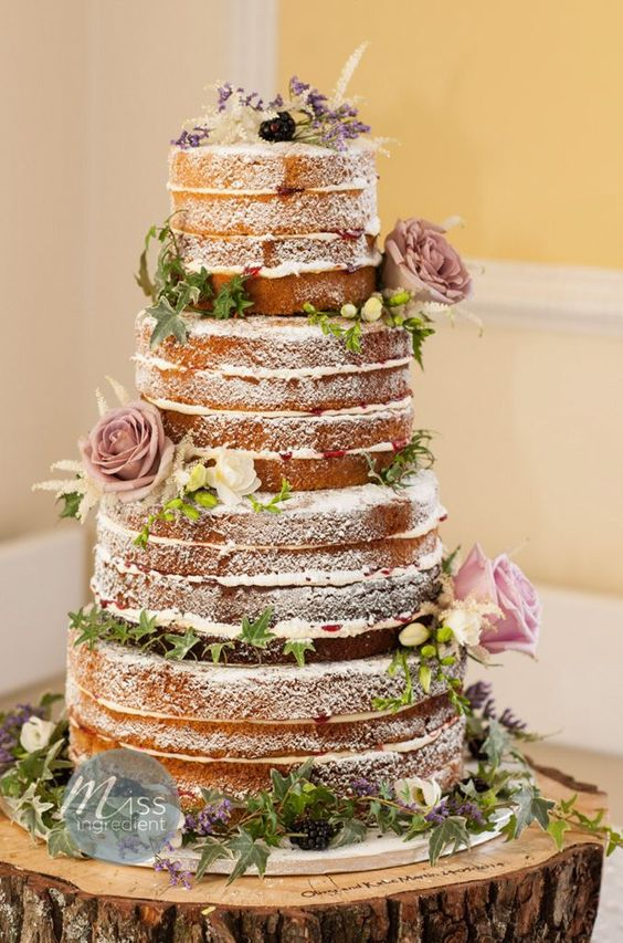 a lovely naked four tier wedding cake with greenery, berries and mauve blooms and dried herbs is a gorgeous idea