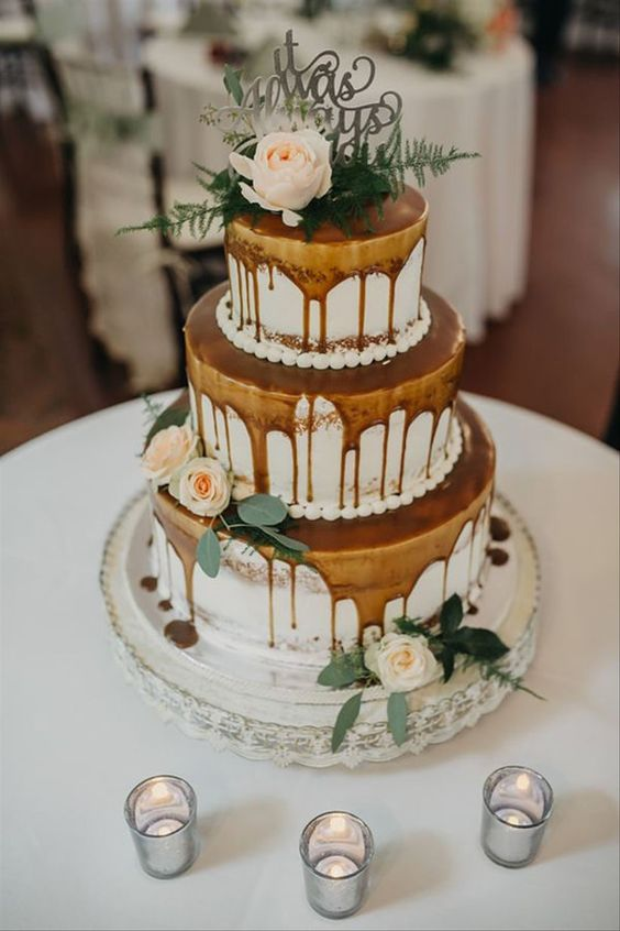 a lovely three-tier naked wedding cake with caramel drip, neutral blooms and greenery and a silver topper is a chic dessert