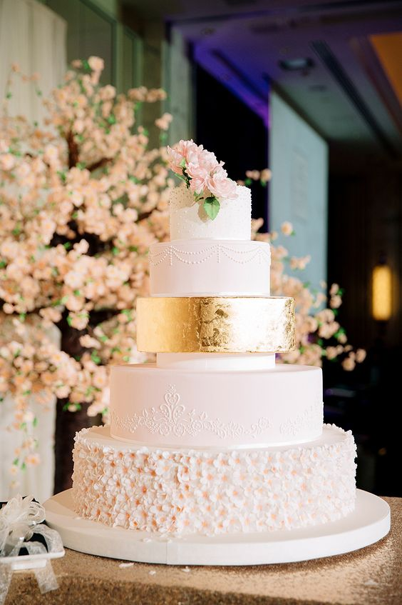 a luxurious five tier wedding cake with textural, floral and gold leaf tiers and pink sugar blooms on top is a wow idea