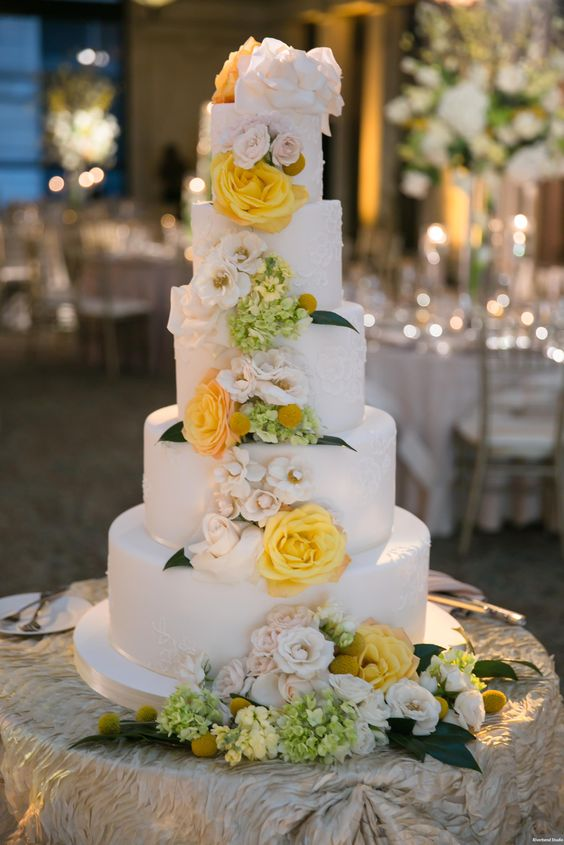 a luxurious five tier wedding cake with textural tiers, white and yellow blooms, greenery and billy balls for spring or summer