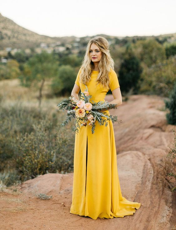 a minimalist mustard A line wedding dress with a front slit, short sleeves and a high neckline for a summer or fall bride