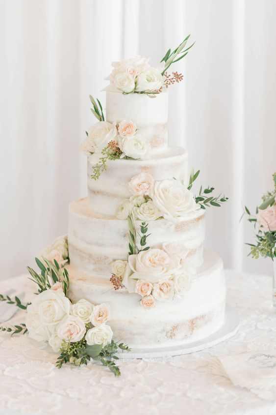 a naked four tier wedding cake with neutral and blush blooms and greenery is a very chic and delicious-looking idea