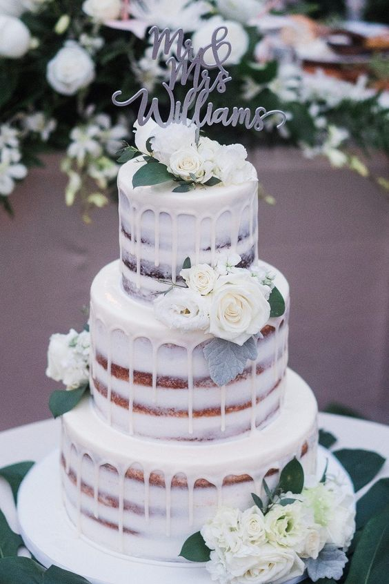 a naked three-tier wedding cake with creamy drip, white blooms and leaves and a calligraphy topper is a delicious option
