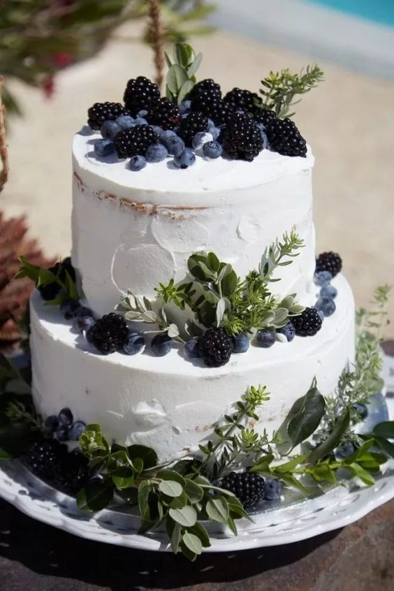 a naked two-tier wedding cake with greenery and berries is a lovely idea to rock at many weddings