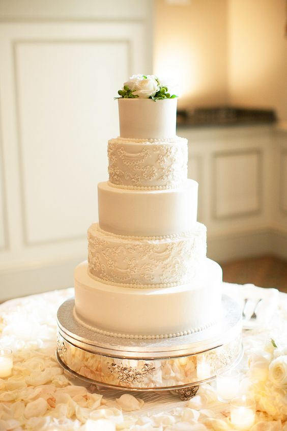 a neutral five tier wedding cake with sleek and textural tiers and some blooms and greenery on top is wow