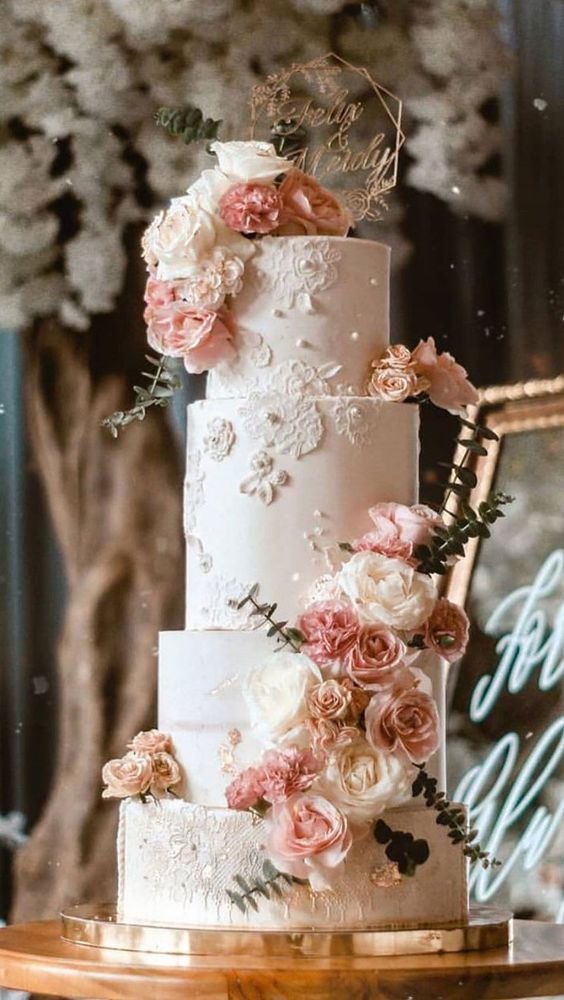a neutral four tier wedding cake with sugar lace appliques, beads and floral patterns, blush and white blooms, beads, greenery and a gold topper