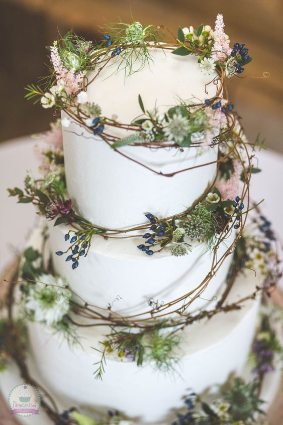 a plain white wedding cake decorated with vine, greenery, berries and pink blooms is ideal for a woodland wedding