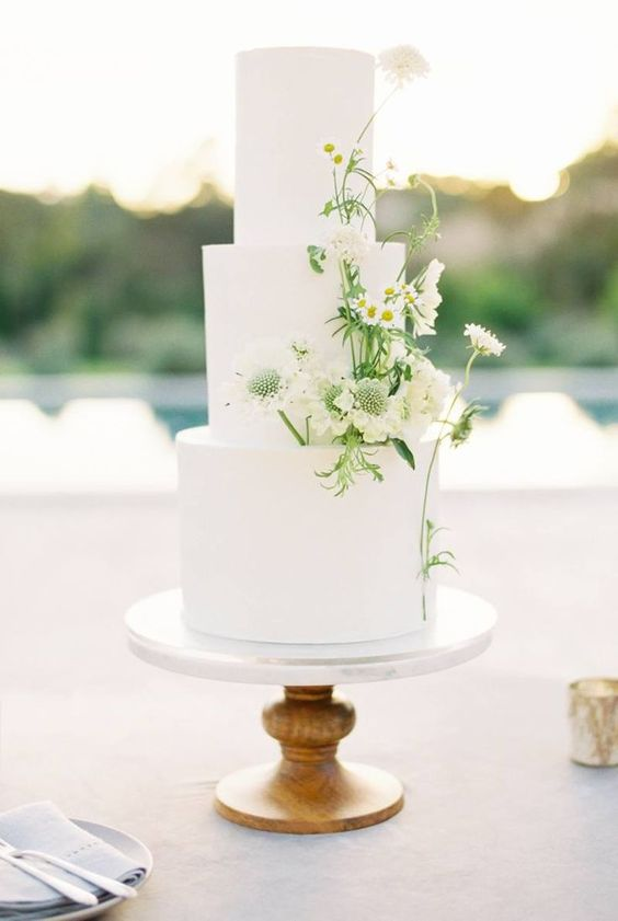 a plain white wedding cake with fresh white blooms and greenery is a refined idea for a spring or summer wedding