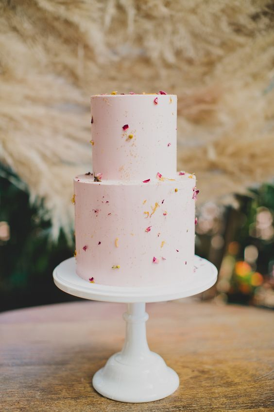 a playful two-tier wedding cake in light pink, with gold speckles and flower petals on it is a perfect idea for spring