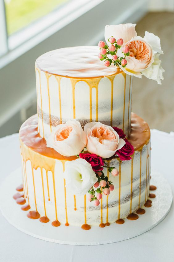 a pretty fall two-tier wedding cake with caramel drip, pastel blooms and berries is a lovely and delicious idea