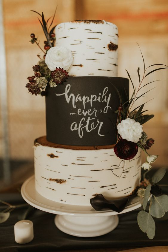 a pretty rustic three-tier wedding cake with birch bark and black tiers, a chalky quote, fresh blooms and greenery is a very lovely idea