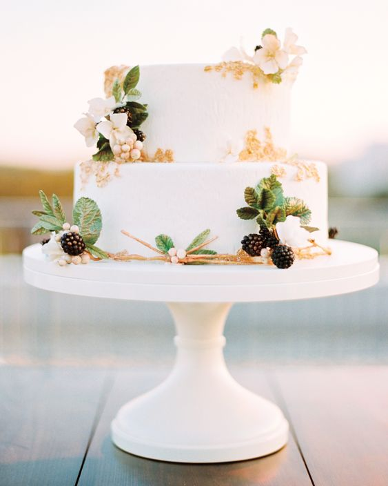 a pretty summer two-tier wedding cake with gold lace, neutral blooms, mint and blackberries is a lovely idea