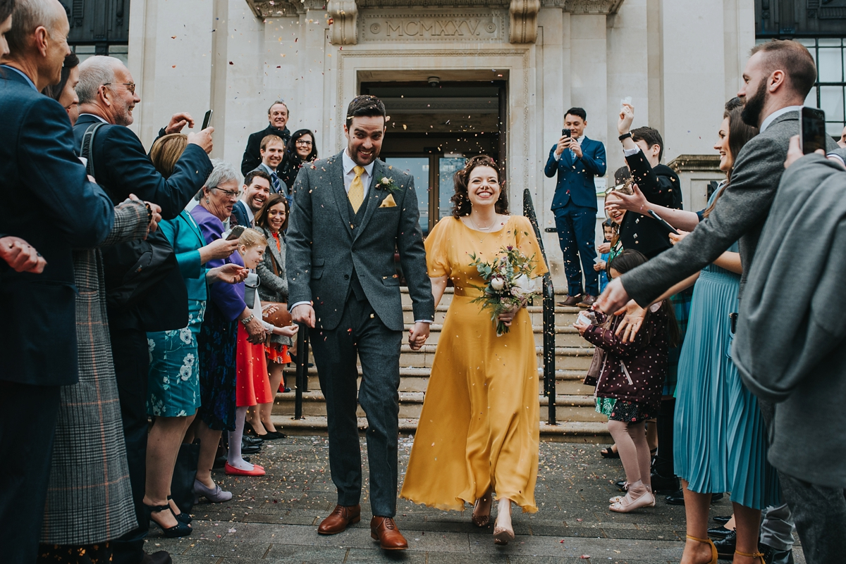 a pretty yellow twirly retro wedding dress with a midi A line skirt, a high neckline and short sleeves plus glitter shoes