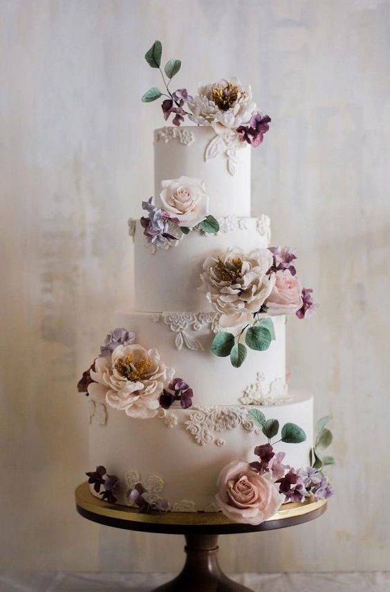 a refined and chic four tier wedding cake with sugar lace, neutral and pastel blooms and greenery is a very stylish dessert