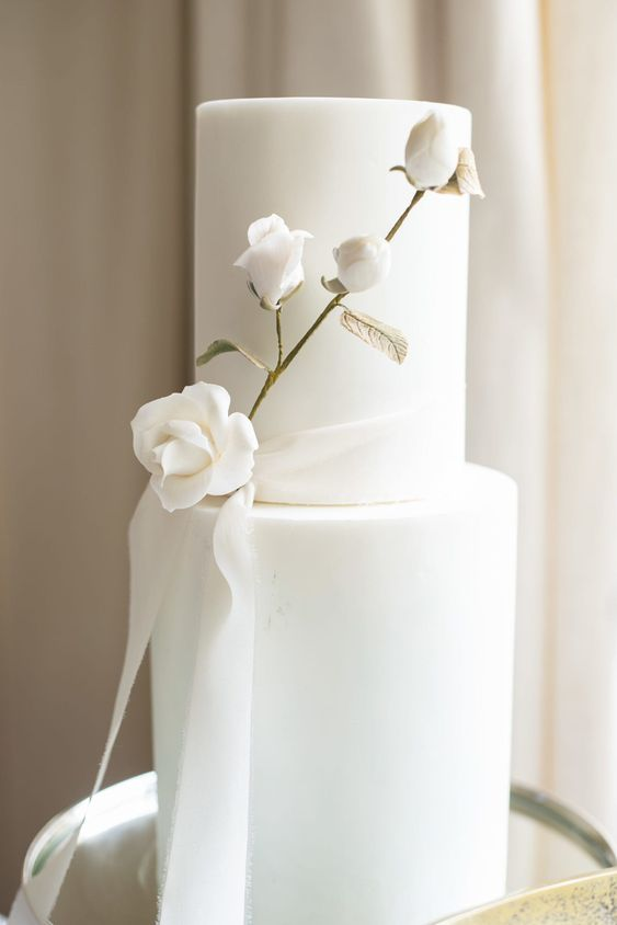 a refined and chic white wedding cake with a white rose branch with a gilded stem and a ribbon is gorgeous